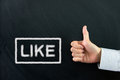 Like thumbs up hand sign on the word written on chalkboard Royalty Free Stock Photos