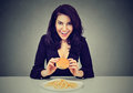 She likes fast food. Happy young woman eating cheeseburger and french fries Royalty Free Stock Photo