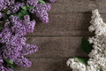 Lilac blossom on rustic wooden background with empty space for greeting message. Top view