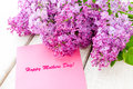 Lilac bouquet with happy mothers day card on wooden table Stock Photo