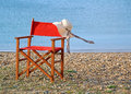 Lilly on the beach photo of a ladies summer hat a deck chair with a gentle sea breeze blowing ribbons while relaxes somewhere Stock Images