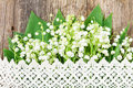 Lilly of valley on wood with lace wooden table Royalty Free Stock Photo