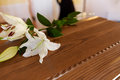 Lily flower on wooden coffin at funeral in church Royalty Free Stock Photo