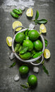 Lime background. Fresh limes in a saucepan with slices and leaves around. Royalty Free Stock Photo
