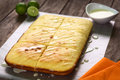 Lime cake with icing fresh homemade key on top on parchment paper and key limes in the back selective focus Stock Images