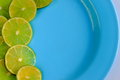 Lime cut into thin slices on a blue plate Stock Photography