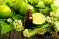 Lime essence bottle with fresh flower and leaves spa concept Royalty Free Stock Photo