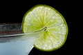 Lime garnish wheel on the rim of a martini glass used as a isolated on a black background Stock Photos
