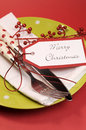 Lime green and red Merry Christmas table place setting. Vertical closeup