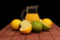 Lime lemon and pitcher of juice on bamboo mat Stock Photo