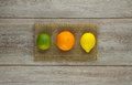 Lime, Orange, Lemon on burlap Stock Photos