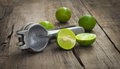 Lime press old hand juicer with limes on wooden background Stock Photography