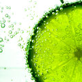 Lime slice in clear fizzy water bubble background isolated Royalty Free Stock Photo