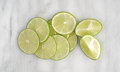 Lime slices and sections on a marble cutting board Royalty Free Stock Photo