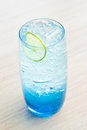 Lime soda glass of ice with blue syrup Royalty Free Stock Images