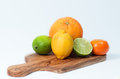 Limes lemon orange and tangerine on a wooden table isolated on white an olive Royalty Free Stock Photo
