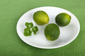 Limes and parsley on white plate on green background Stock Images