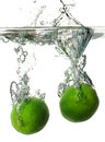 Limes splashing into Water Royalty Free Stock Image