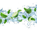 Limes and splashing water over white Stock Photography