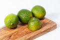 Limes on a wooden table white Royalty Free Stock Photos