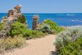 Limestone decorated coastal path vegetated rocks on sandy low dune at cape peron in western australia under a blue sky with an Royalty Free Stock Photos