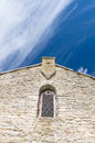 Limestone facade of ancient church with window shutter and cross Royalty Free Stock Photo