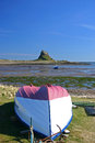 Lindisfarne castle with the harbour and a fishing boat in the foreground Stock Photography