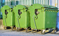 Line green garbage bins against metal fence Stock Photography