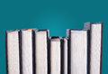 Line of hardcover books lines in a turquoise blue background Royalty Free Stock Image