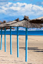 Line of parasols at spanish sand beach vertical shot Stock Photos