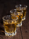 Line of Rum Shots on wooden background Stock Photos