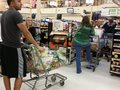 Line of shoppers waiting to check out long at a grocery store pay for their groceries Royalty Free Stock Photography