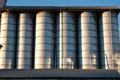 Line of silos row metal under a roof with radent sunlight with contrast and light reflex Royalty Free Stock Image