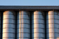 Line of silos row metal under a roof with radent sunlight with contrast and light reflex Royalty Free Stock Images