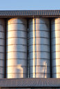 Line of silos row metal under a roof with radent sunlight with contrast and light reflex Stock Images