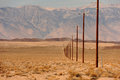 Line of telegraph poles across the desert ws a long power in a straight death valley california Stock Image