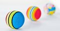 Line of three brightly coloured patterned foan balls foam in a decreasing in focus against a white background Royalty Free Stock Images