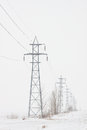Line of Transmission Towers To Horizon in Winter Royalty Free Stock Photo