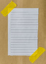 Lined paper scrap on brown with yellow tape Royalty Free Stock Image