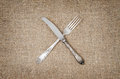 Linen background with fork and knife crossed Royalty Free Stock Photo