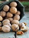 Linen bag with walnuts on wooden background Stock Photography