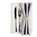Linen textile napkin with cutlery knife and fork serving tabl table setting in silver grey color isolated on white background Stock Photos