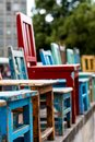 Lineup of colorful wooden chairs of various sizes Royalty Free Stock Photo