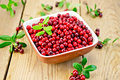 Lingonberry red in bowl on board Royalty Free Stock Photo