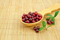 Lingonberry in a spoon on a bamboo mat Stock Photos