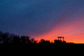 Linha do trator e de árvore no por do sol contra o céu Imagens de Stock