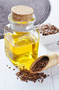 Linseed oil in a glass bottle and flax seeds on a wooden background Royalty Free Stock Photography