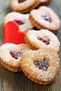 Linzer cookies and red heart on a wooden table Stock Image