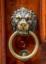 Lion head knocker on an old wooden door Stock Photo