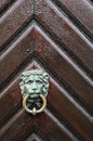 The lion head knocker with the ring on the wooden door Royalty Free Stock Photo